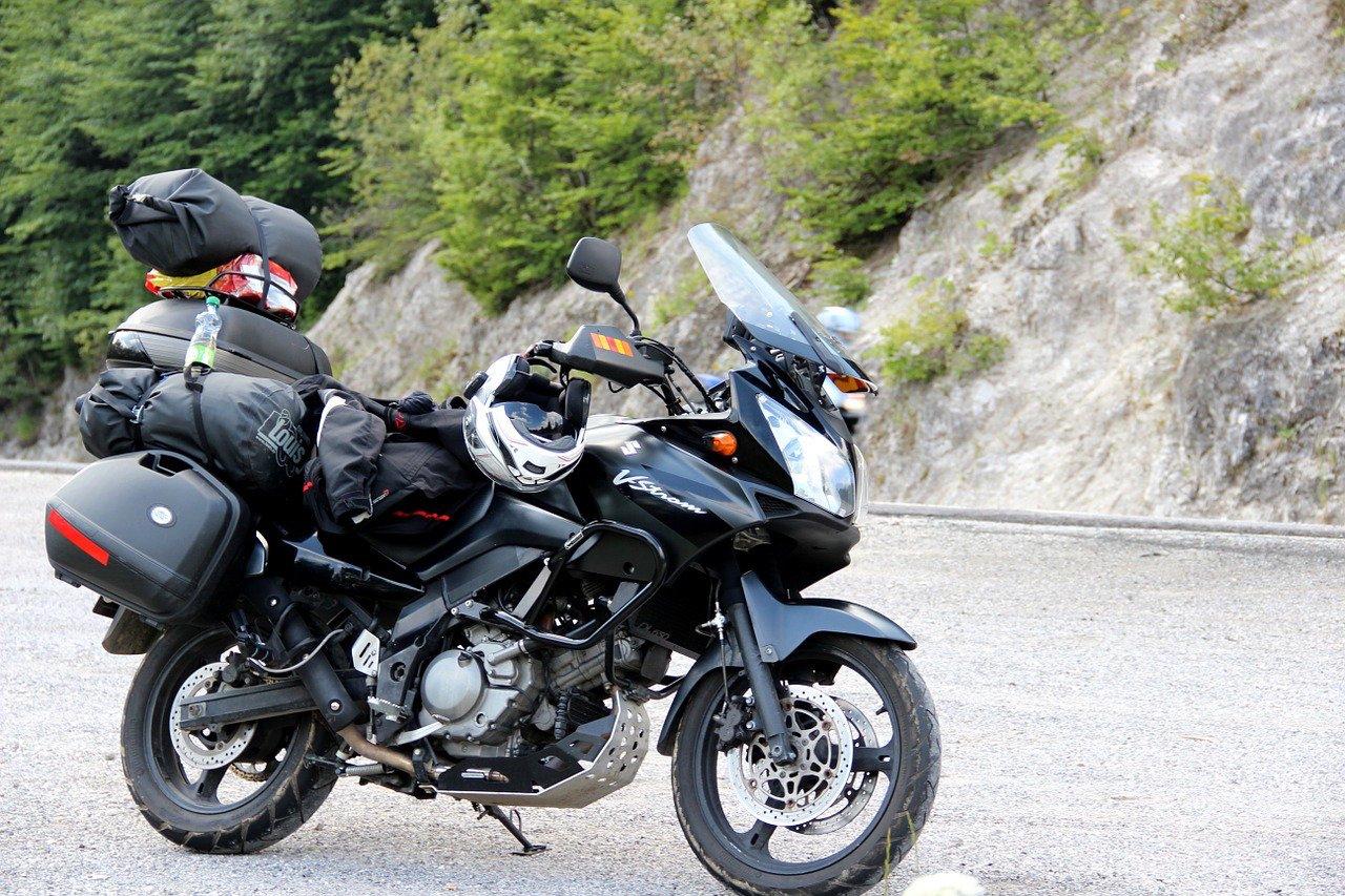 Moto roadster noir de la marque V-Stream lourdement équipé avec boites de rangements et casque