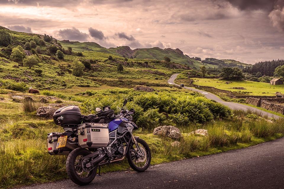 Moto bleu électrique garé sur une longue route au milieu de la nature